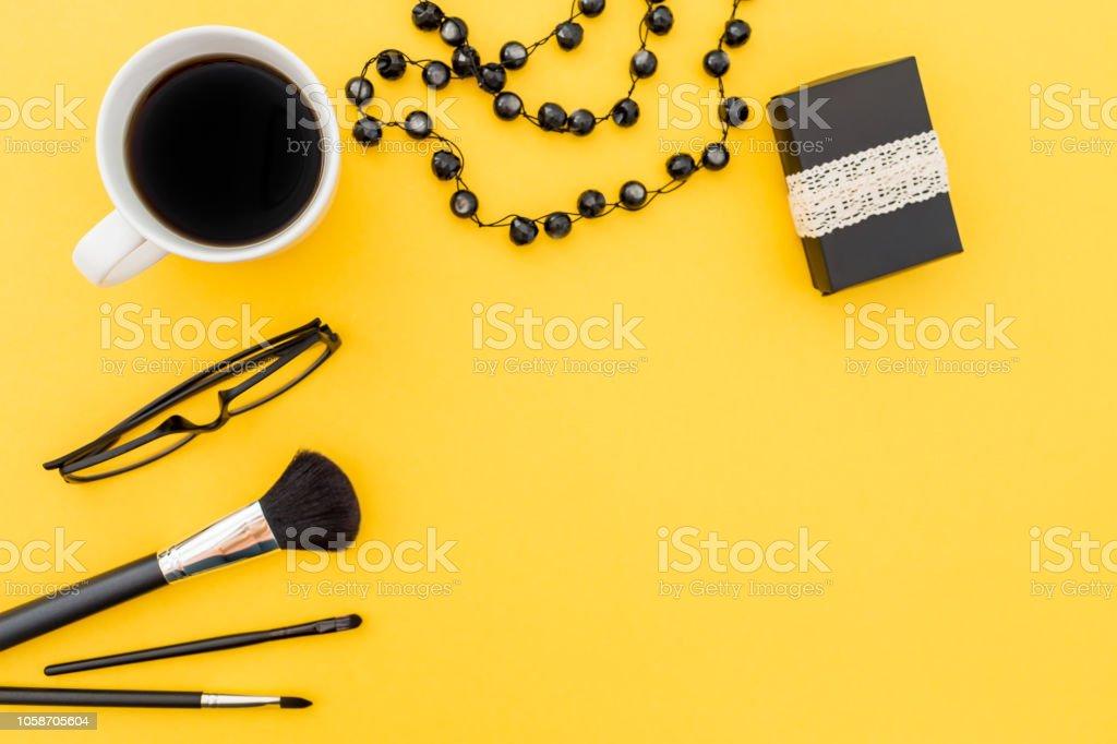 d59a937f7 Caja de regalo, gafas, bisutería y accesorios con taza de café sobre fondo  amarillo
