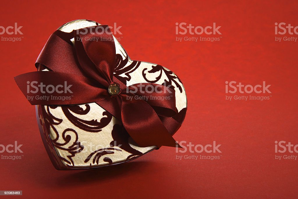 Gift box heart-shaped on red background royalty-free stock photo