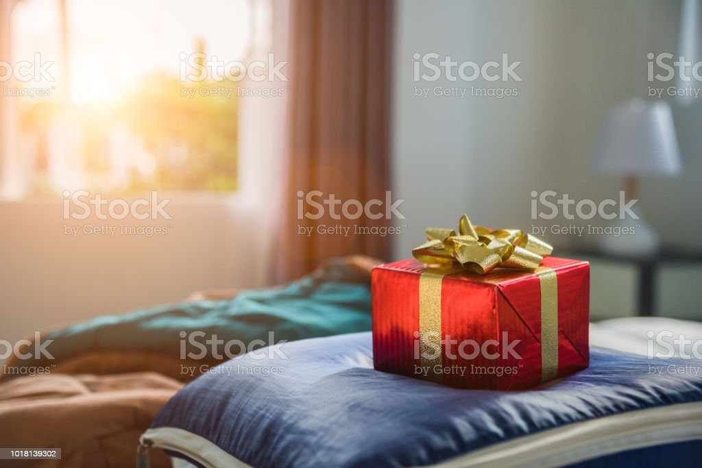 Gift box in bedroom. Holiday and anniversary day concept. Birthday and Valentines day surprise concept. Chirstmas and New year theme. Object and Decoration theme. stock photo