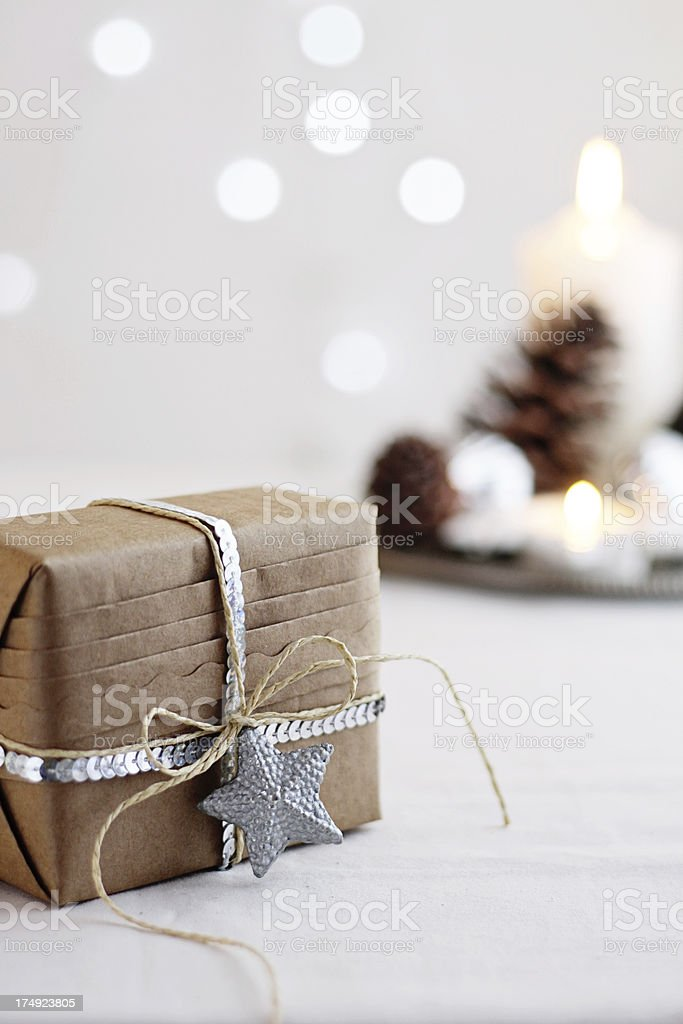 Gift box in brown paper with Christmas decor and lights royalty-free stock photo