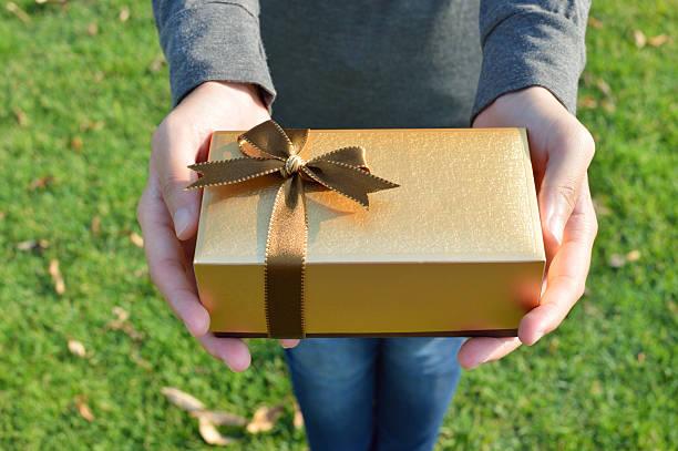 geschenk-box in frau hände auf grünes grass - geheime garten parties stock-fotos und bilder