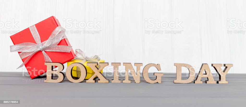 Gift box is tied with a ribbon with words BOXING DAY on wood white background stock photo
