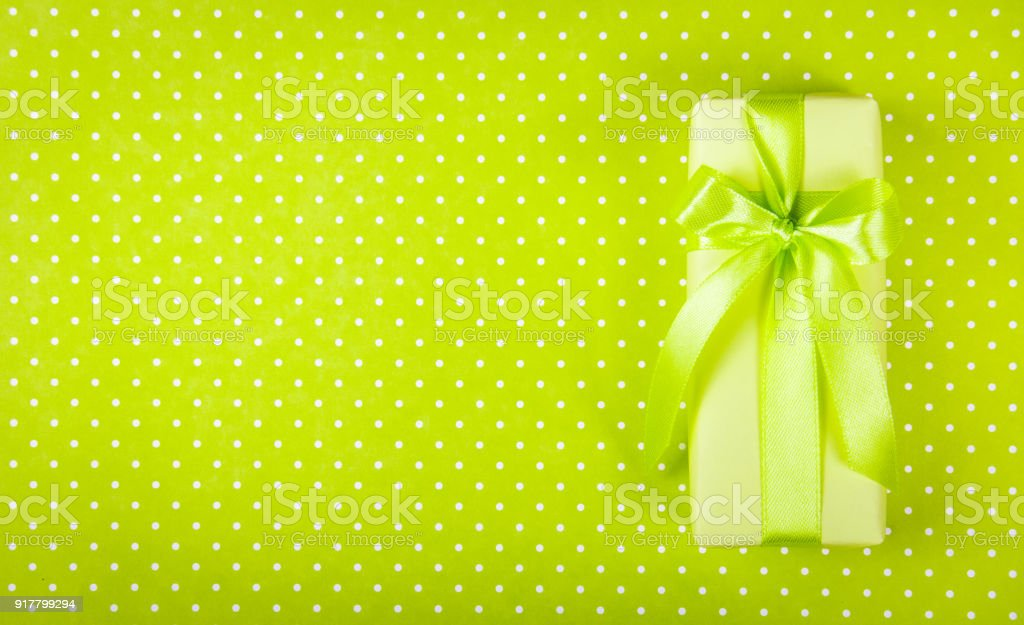 Gift box on light green background. Box with surprise on polka dot...