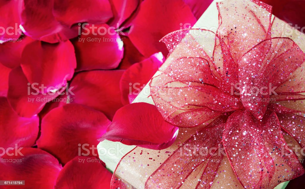 Gift box on red rose petals background stock photo
