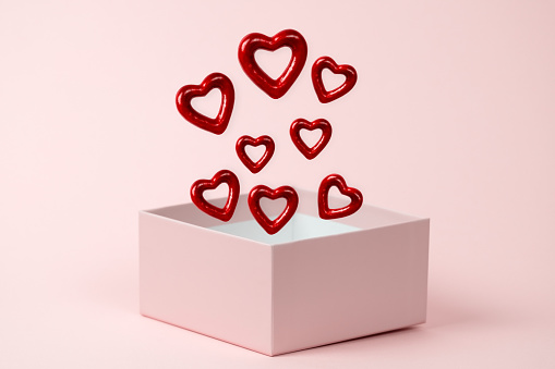 Gift box open with  red hearts floating on a  pink background. Valentines day and love concept.