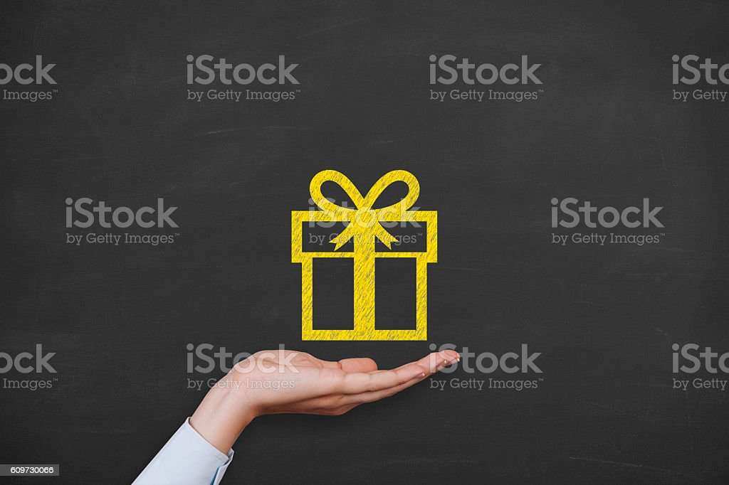 Gift Box over Human Hand on Blackboard stock photo