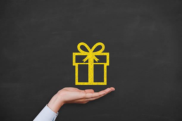 Gift Box over Human Hand on Blackboard stock photo