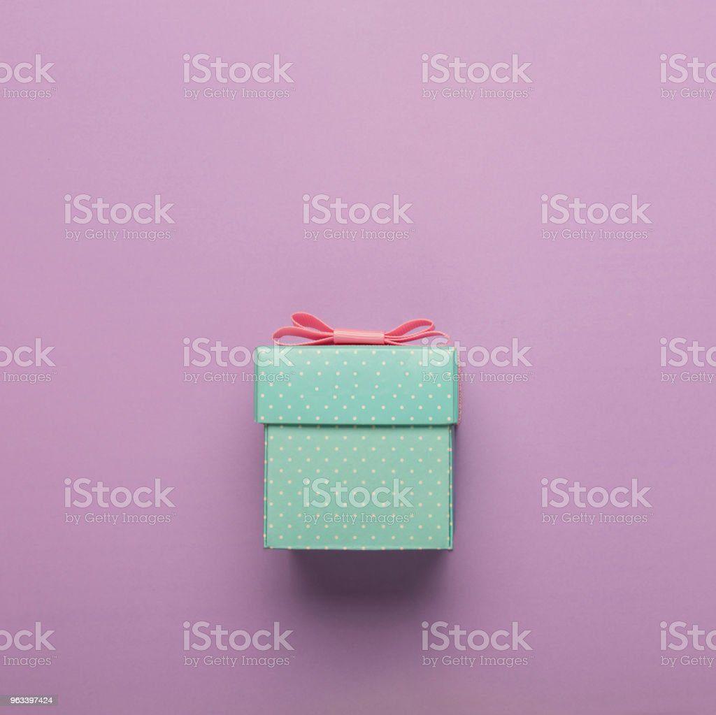 MINIMALISM. turquoise gift box with pink bow on a pink background....