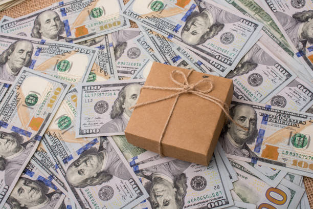 Gift box placed on spread US dollar banknotes stock photo