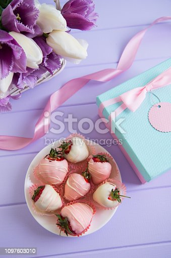 Gift box, strawberry in chocolate on plate, pink ribbon and bouquet of purple and white tulips in wicker basket on lilac table. Romantic surprise for woman or mother.