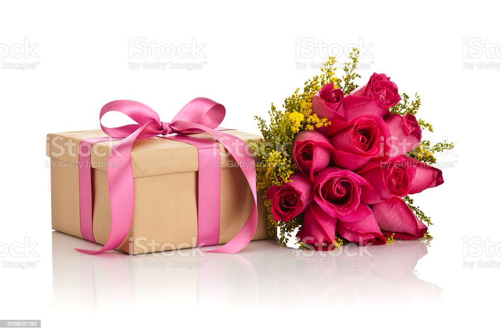 Gift box with a pink bow and a roses bouquet stock photo