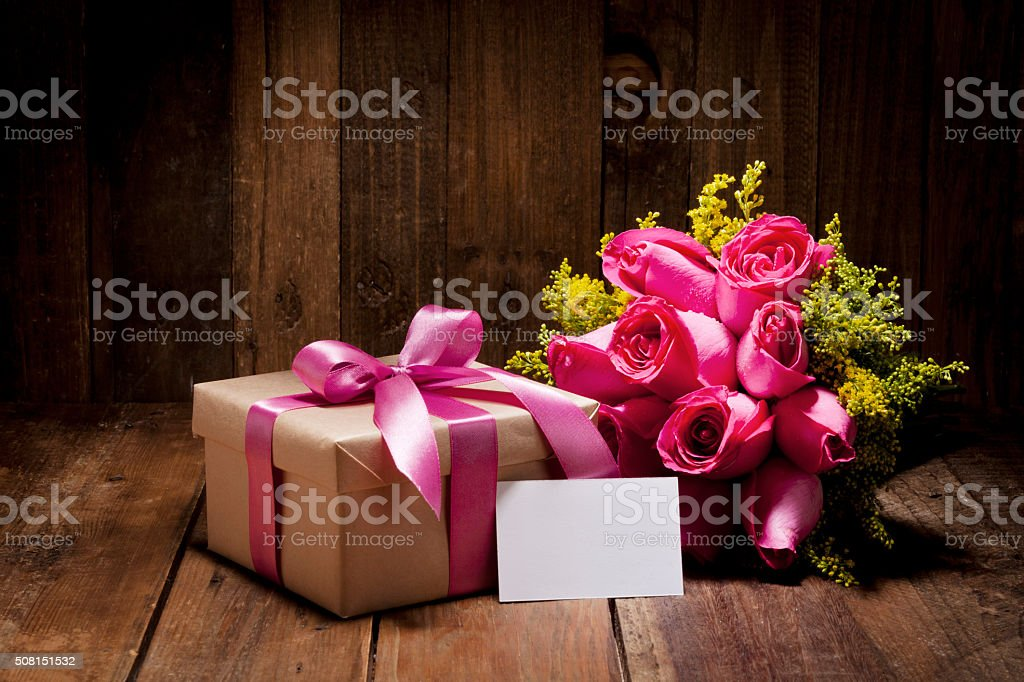 Gift box wrapped with brown craft paper and tied up with pink colored...