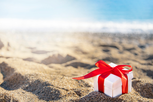 White gift box with a red ribbon standing on the sand with blue sea and sun on background. Holidays on the beach next to the sea.
