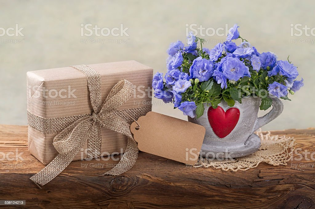Gift box with a tag and flowers stock photo