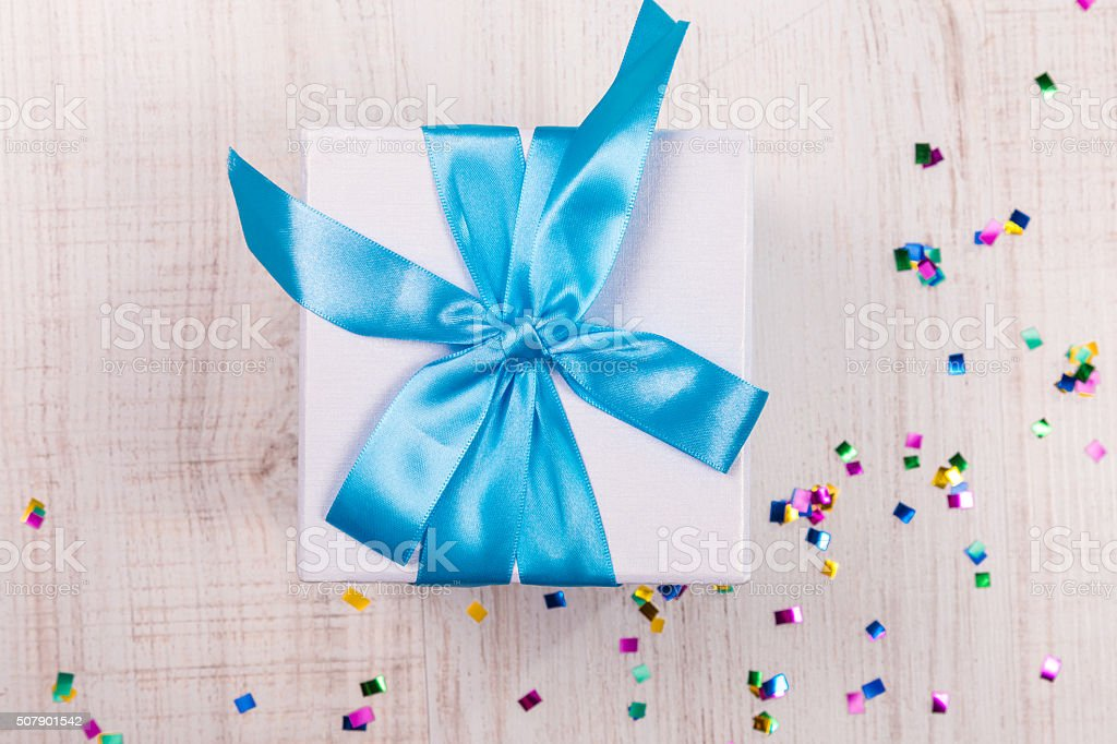 gift box with blue bow on wood table stock photo
