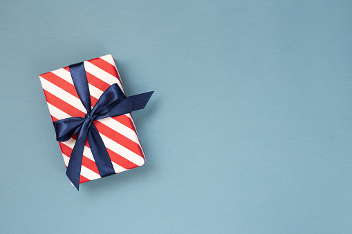 Gift box wrapped in red striped paper and tied with blue bow on blue-gray background. Holiday concept, top view.
