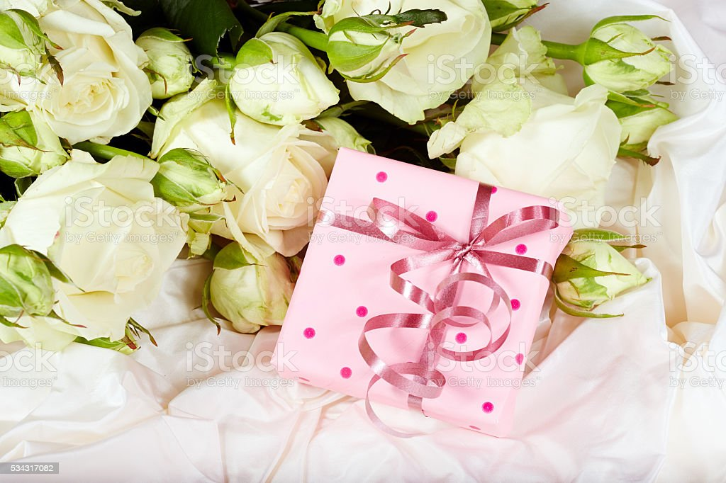 Gift box with bow and white rose flowers, white silk background