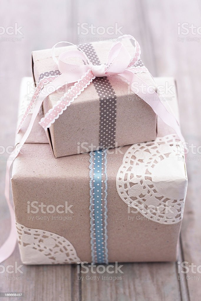 Gift box with brown paper, bows and paper doilies on wood stock photo
