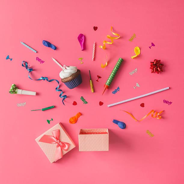 gift box with colorful party items on pink background. - originelle geburtstagsgeschenke stock-fotos und bilder
