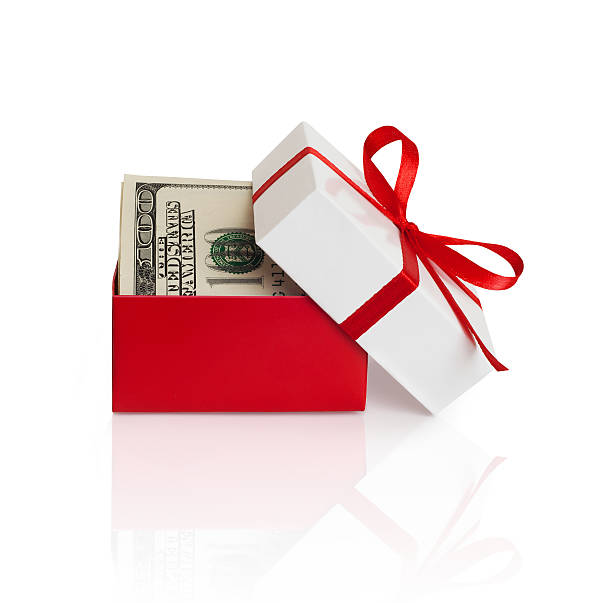 Gift box with money U.S. dollars banknotes laying in red bow decorated gift box. perks stock pictures, royalty-free photos & images