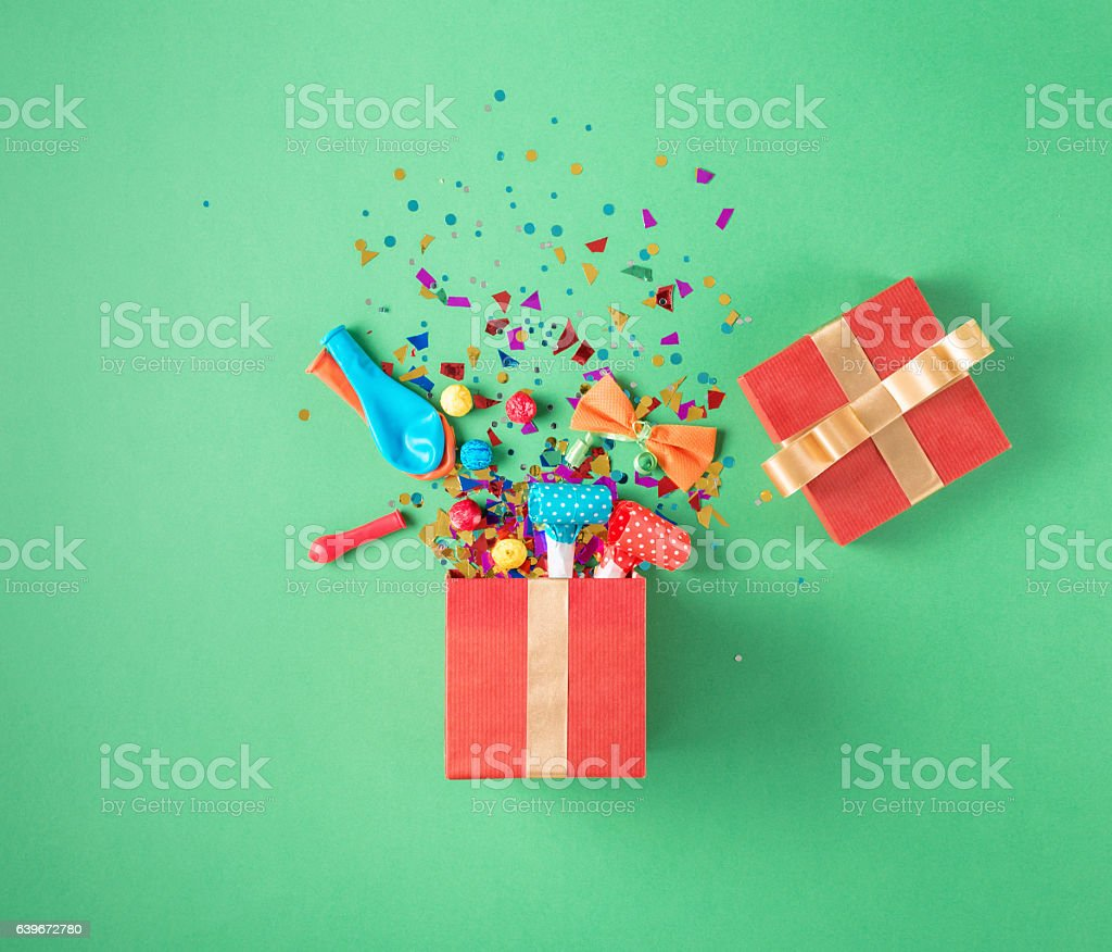 Gift box with party confetti, balloons, streamers, noisemakers stock photo