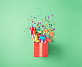 Gift box with party confetti, balloons, streamers, noisemakers,