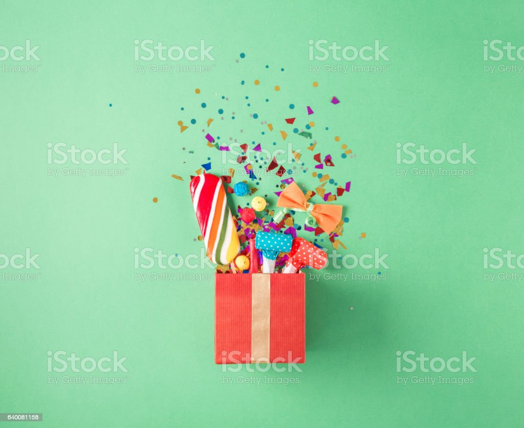 Gift box with party confetti, balloons, streamers, noisemakers, stock photo
