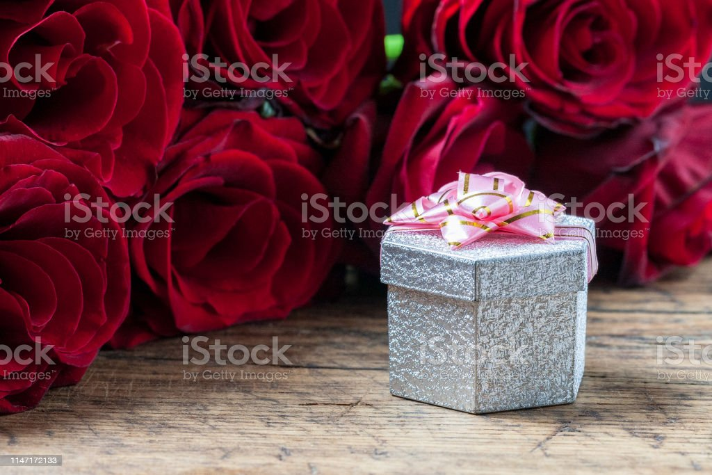 gift box with pink ribbon and red roses behind it at grunge wooden...
