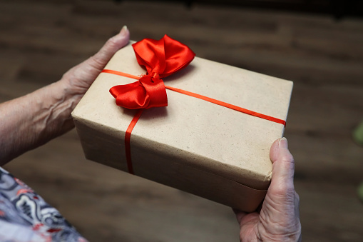 istock gift box with red bow in grandmother hands 656138670