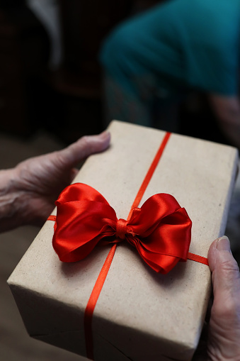 istock gift box with red bow in grandmother hands 656138758