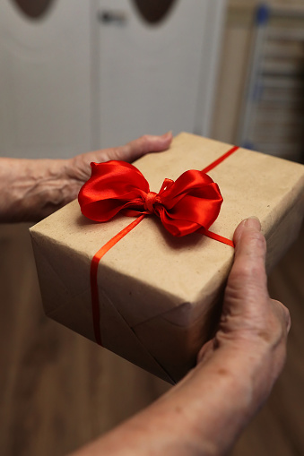 istock gift box with red bow in grandmother hands 656138792