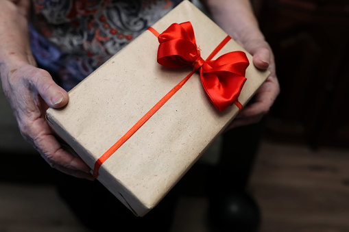 istock gift box with red bow in grandmother hands 656138854