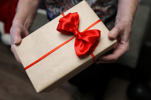 istock gift box with red bow in grandmother hands 656138904