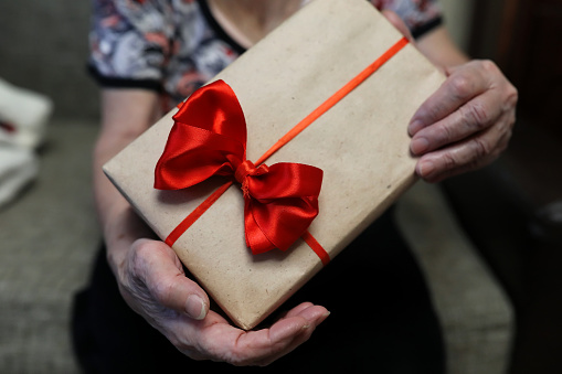 istock gift box with red bow in grandmother hands 865556212