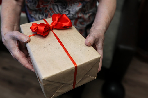 istock gift box with red bow in grandmother hands 865556234