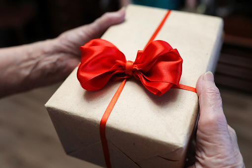 istock gift box with red bow in grandmother hands 887109568