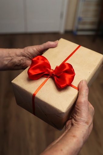 istock gift box with red bow in grandmother hands 887109634