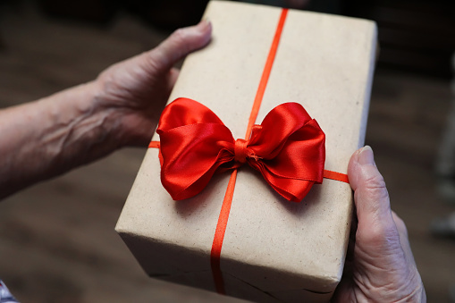 istock gift box with red bow in grandmother hands 898865876