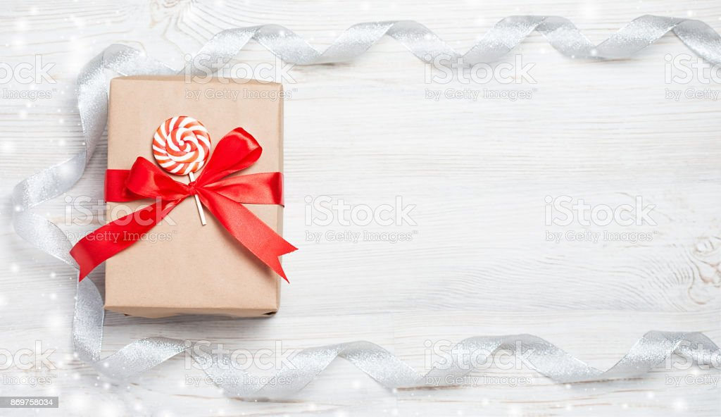 Geschenk-Box mit roter Schleife auf Holztisch. Weihnachten Hintergrund mit festlichen Dekoration. Platz für Ihren Text. Exemplar. Ansicht von oben flach zu legen – Foto