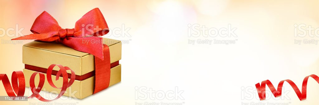 Gift box with red ribbon bow and red rose flowers on holiday bokeh...