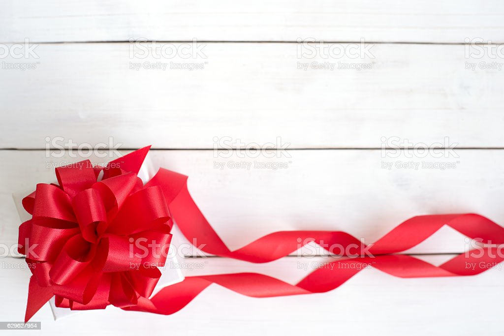 Gift box with red ribbon bow on wooden white background stock photo