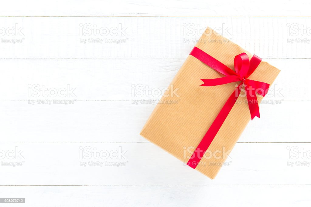 Gift box with red ribbon on white wood background stock photo