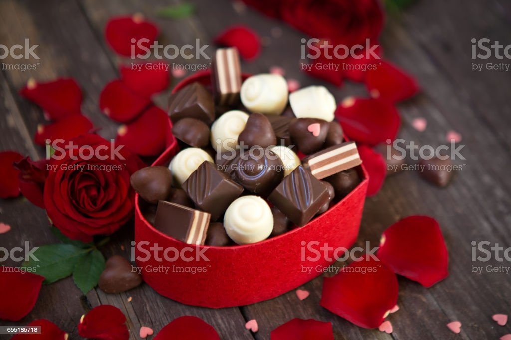 Gift box with red roses and chocolates on wooden background stock photo