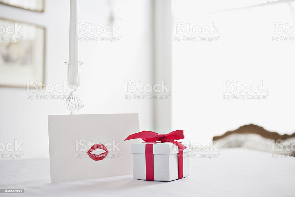 Gift box with ribbon and card with lipstick kiss on desk stock photo
