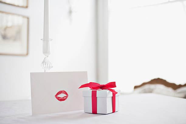 geschenkbox mit schleife und karte mit lippenstift-kuss auf schreibtisch - romantische karten stock-fotos und bilder