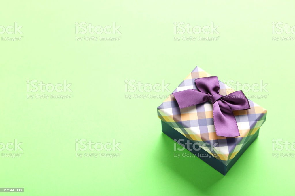 Gift box with ribbon on green background royalty-free stock photo