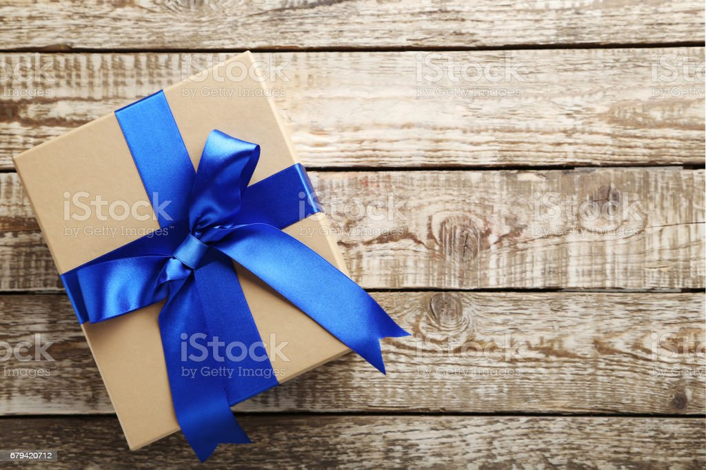 Gift box with ribbon on grey wooden table stock photo