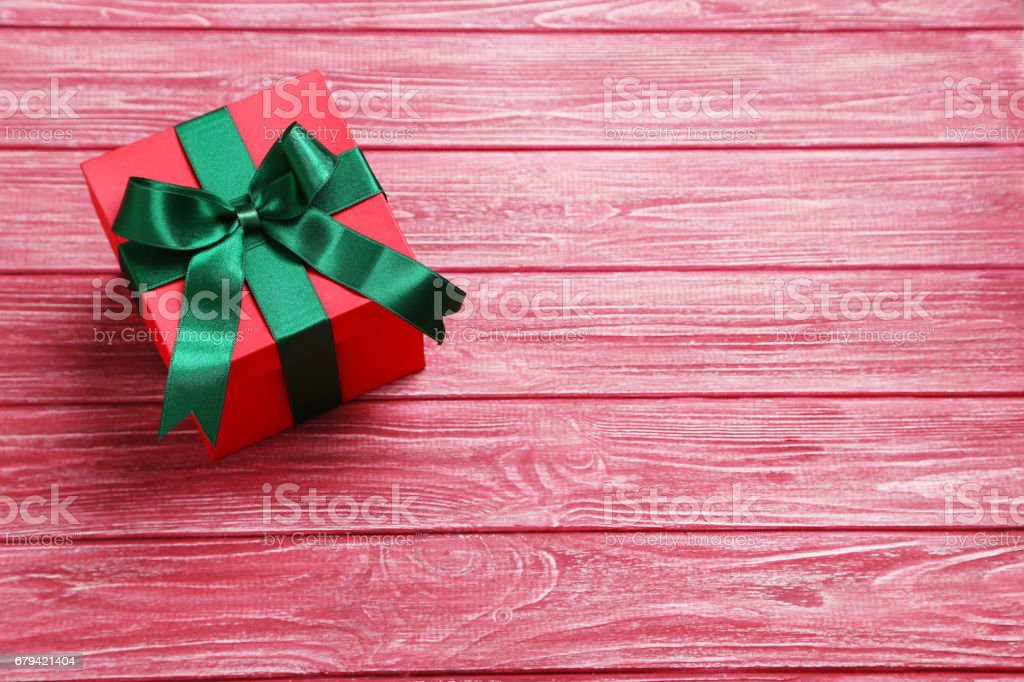 Gift box with ribbon on red wooden table foto de stock royalty-free