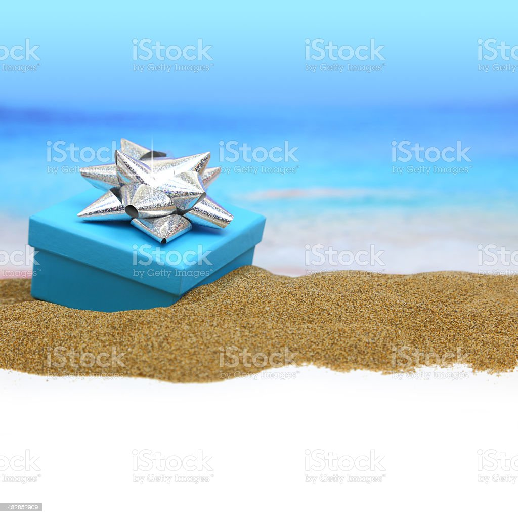 Gift box with ribbon on the sand stock photo