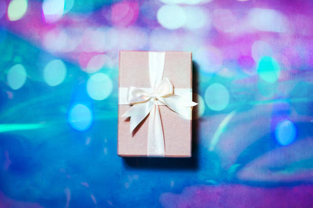 gift box with ribbon over holographic background. minimal flat lay in neon light - gradients golden ribbons imagens e fotografias de stock